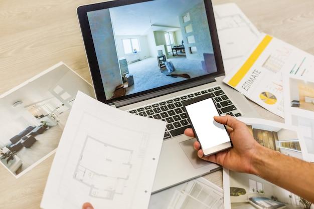Biurko inżyniera budowlanego i architekta z widokami z domu, laptopem, narzędziami i próbkami drewna
