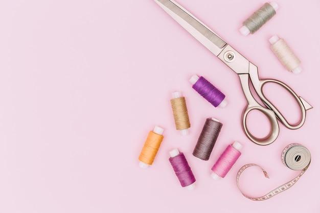 Biurko krawieckie. dodatki krawieckie i tkanina na różowym tle. nici szwalnicze, igły, tkanina, centymetr krawiecki lub taśma miernicza. widok z góry. miejsce.