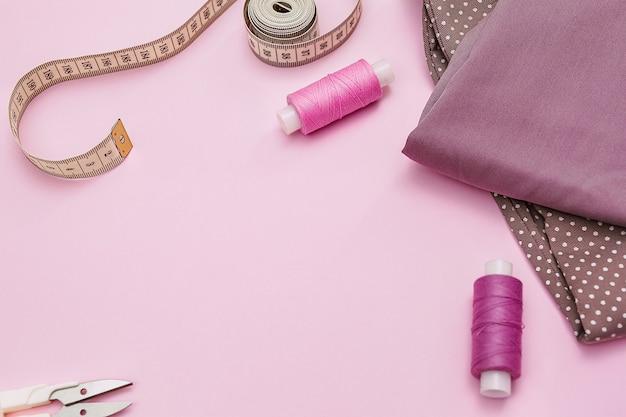 Biurko krawieckie. dodatki krawieckie i tkanina na różowym tle. nici szwalnicze, igły, tkanina, centymetr krawiecki lub taśma miernicza.