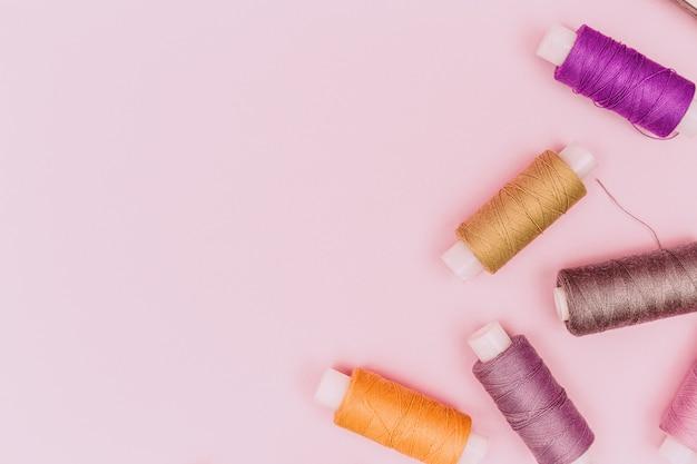 Biurko krawieckie. krawiec lub haft tła. wzór kolor nici do szycia lub szpule na różowym tle, lato widok z góry. kolorowe wątki