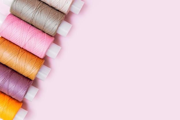 Biurko krawieckie. krawiec lub haft tła. wzór kolorowych nici do szycia lub rolek na różowym tle, widok z góry copyspace