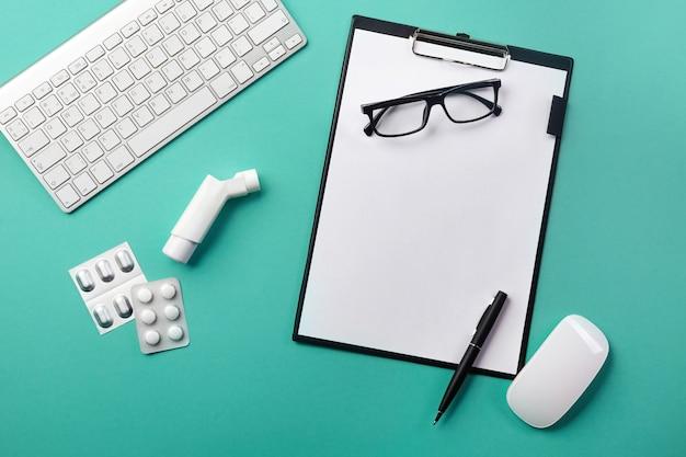 Biurko lekarzy z tabletem, długopisem, inhalatorem i tabletkami. widok z góry z miejscem na twój tekst.