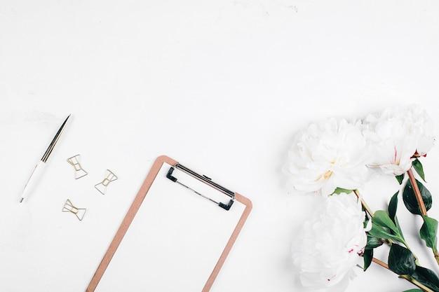 Biurko na biurko. miejsce pracy z kwiatami piwonii, schowkiem i piórem. widok z góry, makieta, miejsce. notatki lub koncepcja planowania