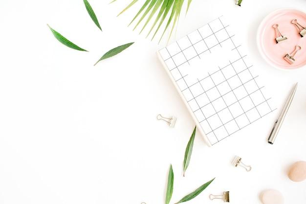 Biurko na biurko z widokiem z góry na płasko. obszar roboczy z notatnikiem, gałązką palmową i klipsami na białym tle.