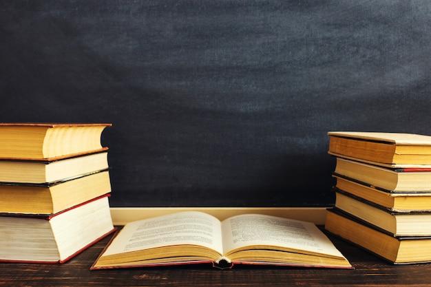 Biurko na tle tablic kredowych i książek.