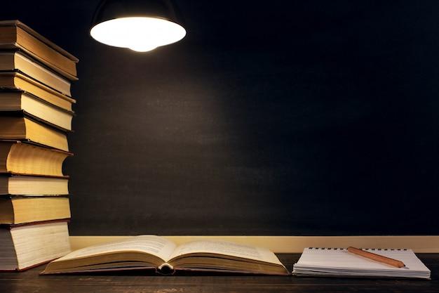 Biurko na tle tablicy kredowej, książek, notesu i długopisów, w ciemności w świetle lampy.