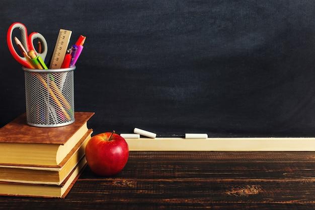 Biurko nauczyciela z materiałami do pisania, książką i jabłkiem, puste miejsce na tekst lub tło dla motywu szkolnego.