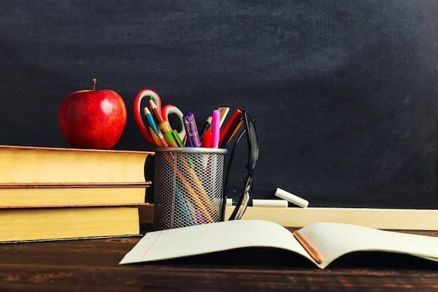 Biurko nauczyciela z materiałami do pisania, książką i jabłkiem