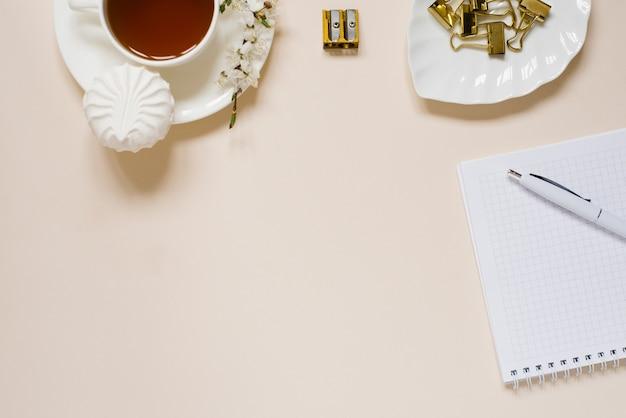 Biurko nowoczesnej kobiety, biuro w domu. notatnik, herbata, wiosenne kwiaty jabłoni na jasnym stole. minimalna koncepcja biznesowa, płasko świecki, miejsce na tekst.