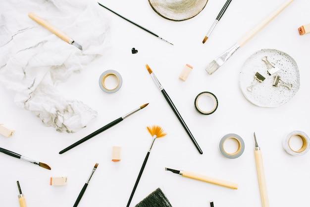 Biurko obszaru roboczego biura domowego artysty z pędzle i narzędzia na białym tle.