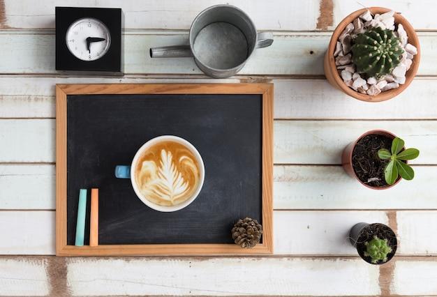 Biurko ogrodnicze leżące na płasko z tablicą, zegarem, kaktusami i filiżanką kawy na drewnie vintage