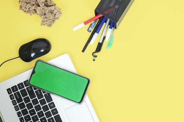 Biurko pełne papeterii na żółtym tle