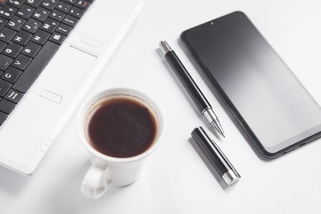 Biurko. smartfon, klawiatura, kawa, długopis.