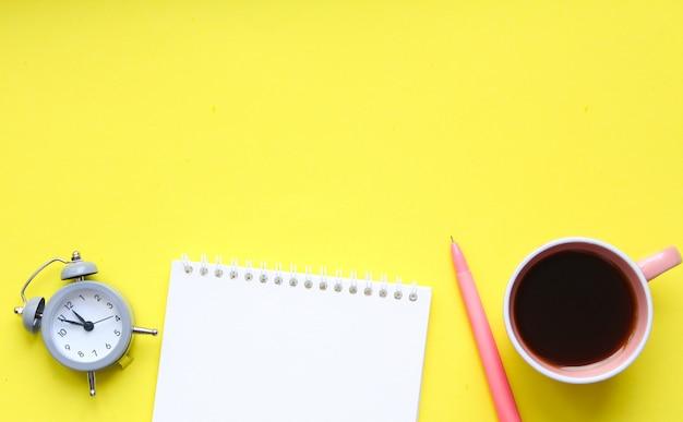 Biurko studenckie z dostawami, notatnikiem, filiżanką kawy, piórem, mini budzikiem.