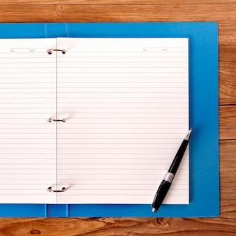 Biurko studenta z niebieskim folderem projektu