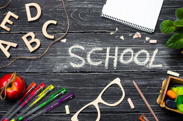 Biurko ucznia na tablicy szkolnej, ciemne drewniane tło z desek.