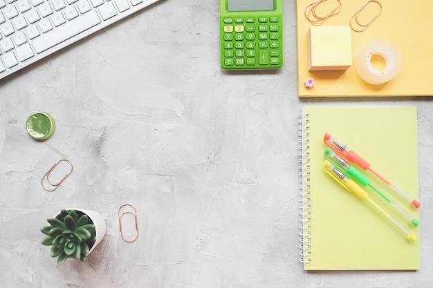 Biurko w biurze domowym freelancer z laptopem, notatnikiem, soczystą rośliną, kalkulatorem na szaro, płasko