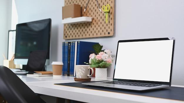 Biurko w biurze domowym z laptopem i materiałami biurowymi.