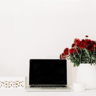 Biurko w domu z laptopem, piękny bukiet czerwonych kwiatów, biała trumna vintage przed białym tłem