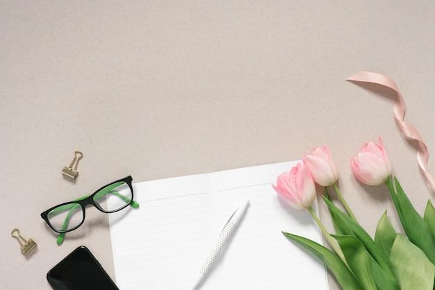 Biurko w różowych, zakurzonych kolorach, telefon, różowe tulipany, okulary, czyste strony otwartego pamiętnika