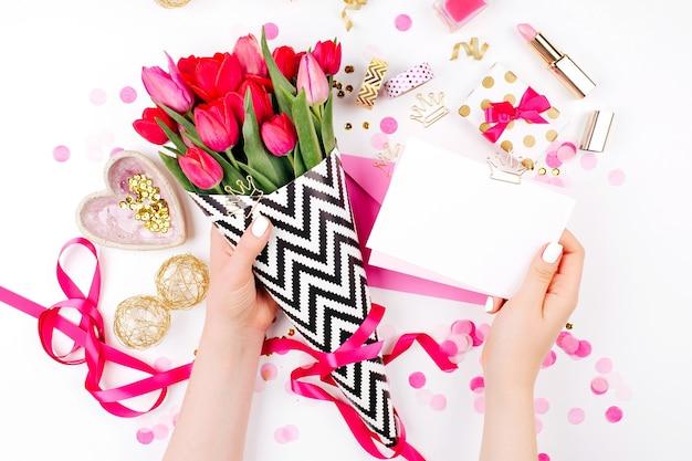 Biurko w różowym i złotym stylu z kwiatami. kobiece ręce trzymają kartę