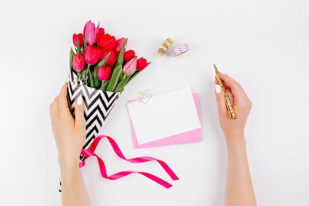Biurko w różowym i złotym stylu z kwiatami. kobiece ręce trzymają kwiaty