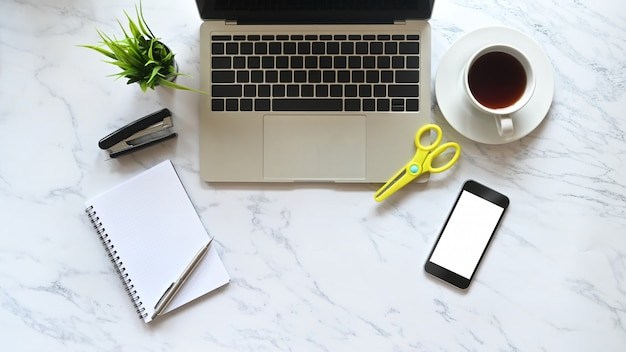 Biurko widok marmurowy stół laptop, kawa, smartfon i materiały biurowe.