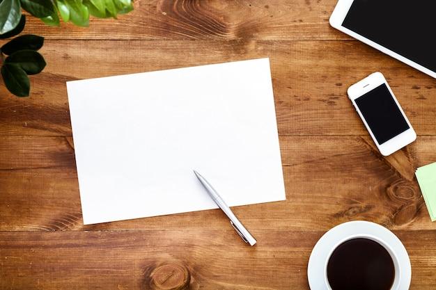 Biurko z białym czystym arkuszem papieru na długopisy i urządzenia