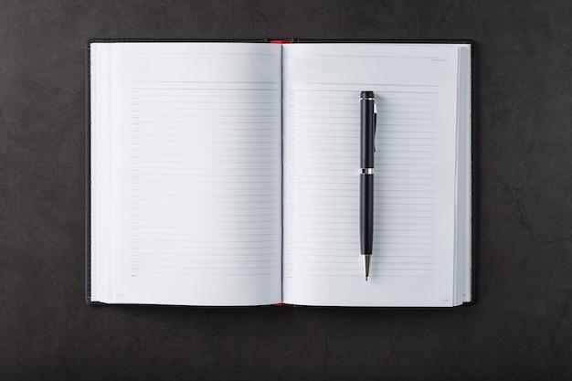 Biurko z czarnym notatnikiem i długopisem na czarnym tle. widok z góry z miejscem na kopię. cele biznesowe i koncepcja założeń
