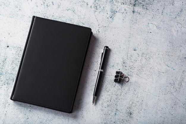 Biurko z czarnym notesem i długopisem na szarym tle. widok z góry z miejscem na kopię. cele biznesowe i koncepcja założeń