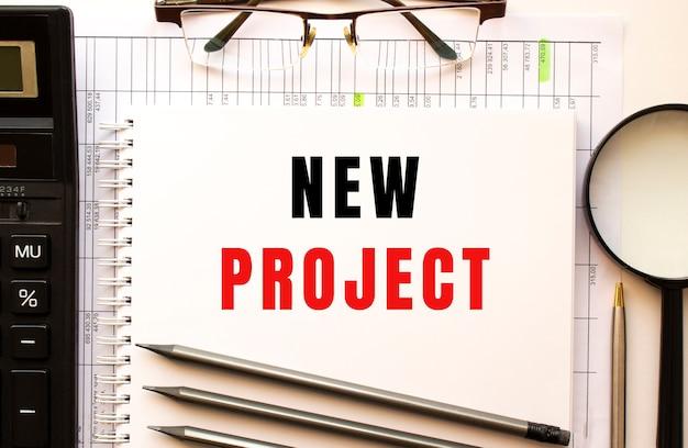 Biurko z dokumentami finansowymi strona notatnika z napisem nowy projekt