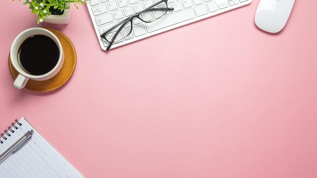 Biurko z kawową klawiaturą notebooka okulary na różowym tle. skopiuj miejsce.
