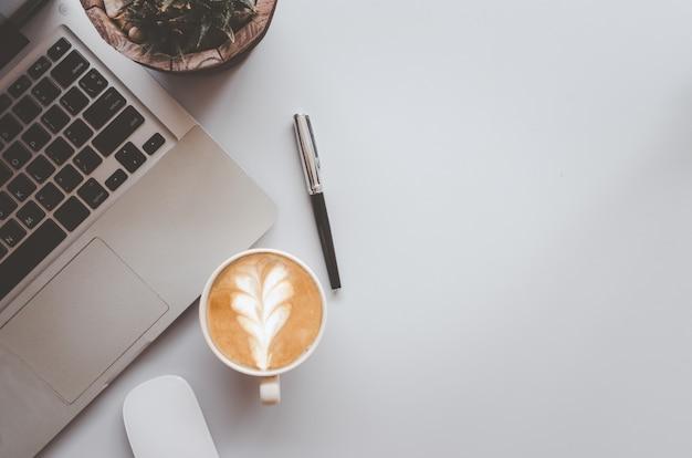 Biurko z klawiaturą, komputerem, piórem, kawą i myszą na szarym tle. widok z góry z miejscem na kopię. koncepcja biznesu i finansów. płaskie lay.