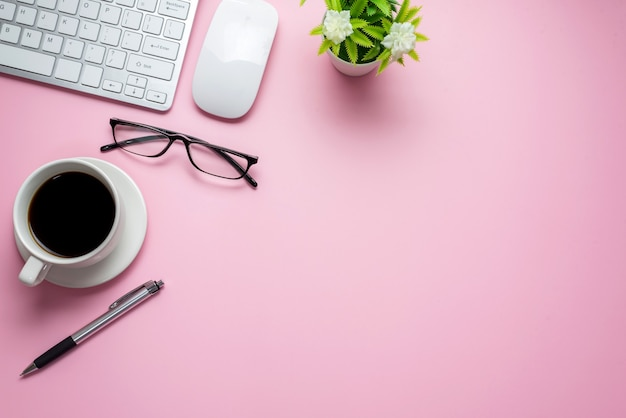 Biurko z klawiaturą notebooka okulary umieszczone na różowym stole, kopia przestrzeń.