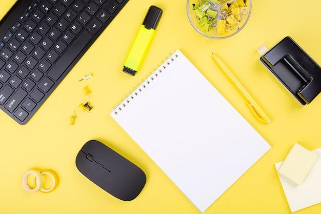 Biurko z komputerem i papeterii, żółte tło.