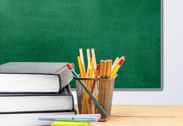 Biurko z książką i papeterią na tle tablicy. powrót do koncepcji szkoły