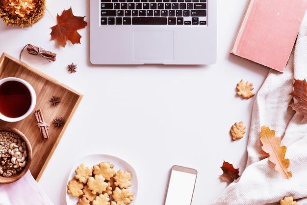 Biurko z laptopem, filiżanką kawy, ciastkami, książką i jesiennymi liśćmi. widok z góry