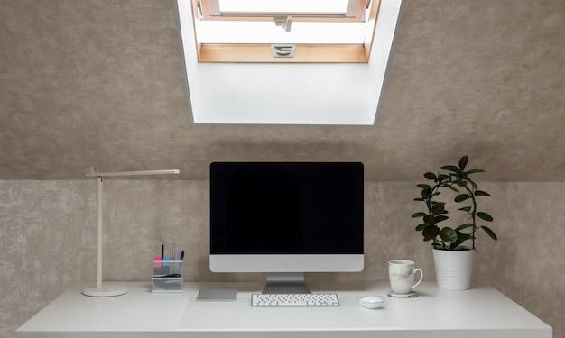 Biurko z monitorem, lampką stołową i kubkiem do kawy, pracująca przerwa na kawę w domu poziomo