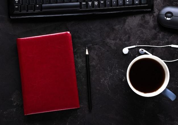Biurko z notatnikiem, kubkiem kawy lub herbaty, klawiaturą, myszką, słuchawkami i ołówkiem