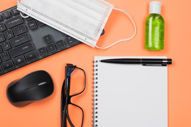 Biurko z notatnikiem, myszką komputerową, klawiaturą i odkażaczem do rąk