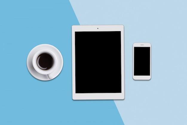 Biurko z nowoczesnym tabletem, smartfonem i filiżanką kawy. widok z góry nowoczesnych gadżetów leżących na niebiesko. nowoczesne technologie, komunikacja, zawód i koncepcja pracy biurowej