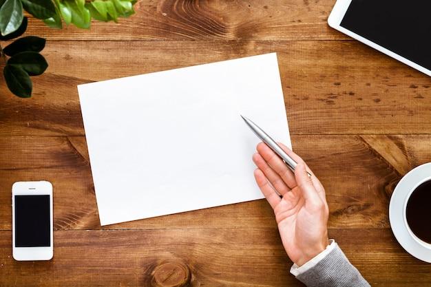 Biurko z otwartym pustym notatnikiem na notatki na brązowym drewnianym stole