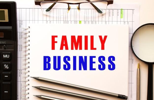 Biurko z papierami finansowymi, lupą, kalkulatorem, okularami. strona w notatniku z napisem family business. widok z góry. pomysł na biznes.