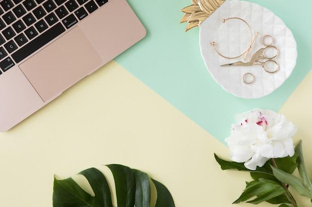 Biurko z pastelowym biurkiem z laptopem komputerowym, zielonymi liśćmi palmowymi, kwiatami, schowkiem i akcesoriami kosmetycznymi, widok z góry i leżał płasko. domowych mod kobiet biurowy workspace odizolowywający na żółtym tle.