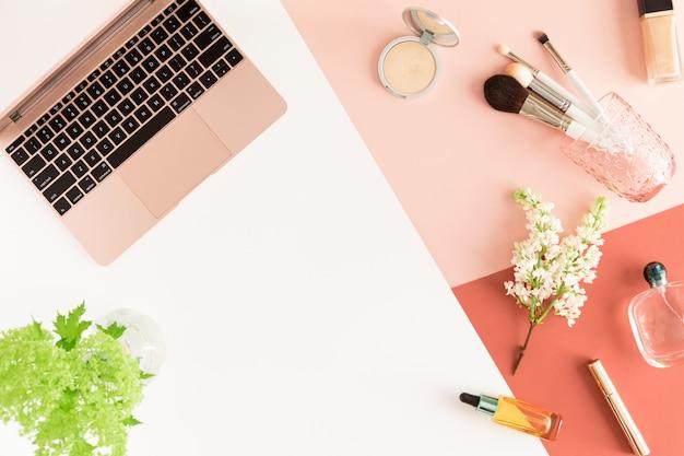 Biurko z pastelowym biurkiem z laptopem, liśćmi, wiosennymi kwiatami, schowkiem i kosmetykami, widok z góry