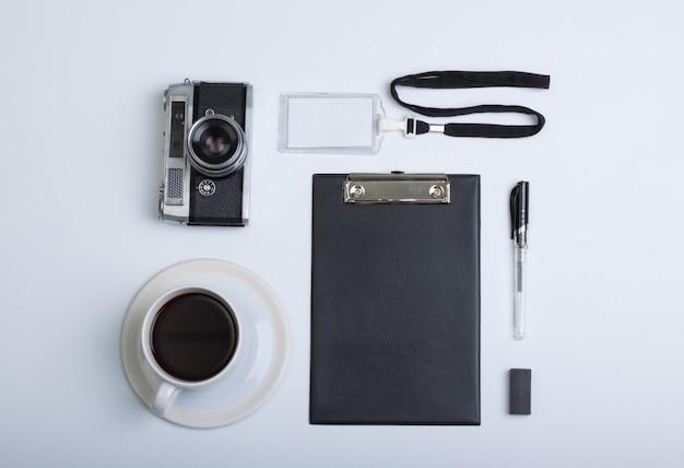 Biurko z płaskim blatem, widok z góry. biała filiżanka kawy, długopis, aparat fotograficzny i schowek na białym tle