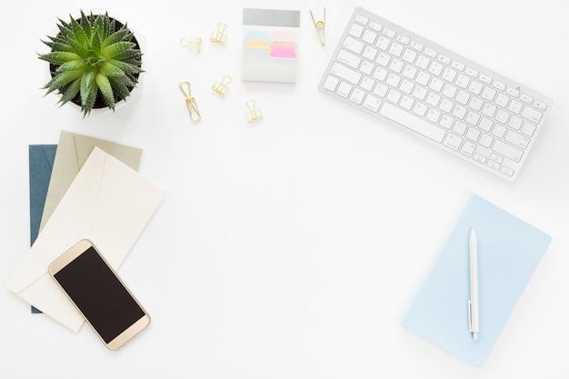 Biurko z płaskim stołem i biurkiem w widoku z góry. obszar roboczy z pędzel, laptop, bukiet kwiatów bzu, szpula z beżową i niebieską wstążką, pamiętnik mięty na białym tle.