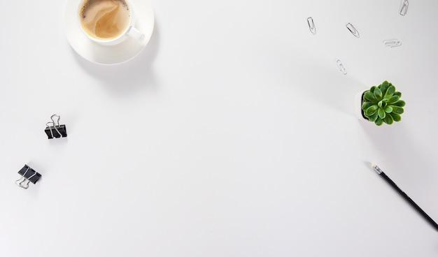 Biurko z płaskim stołem i biurkiem w widoku z góry. obszar roboczy z pustą deską do pisania, artykułami biurowymi, ołówkiem, zielonym liściem i kawą