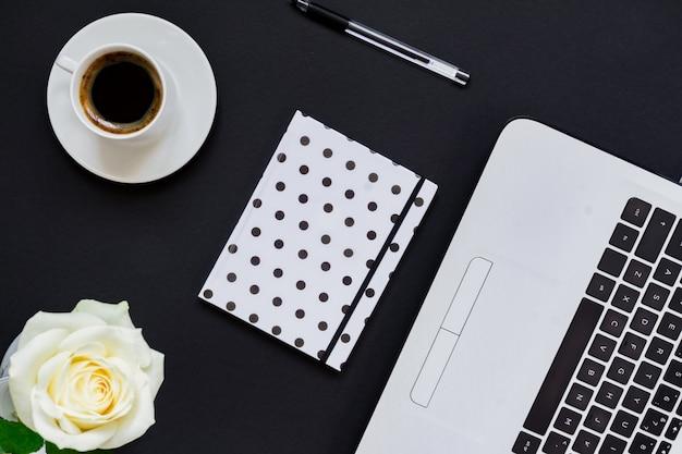 Biurko z płaskim stołem, widok z góry. miejsce do pracy z laptopem, białą różą, pamiętnikiem w kropki i kubkiem kawy na czarnym tle.