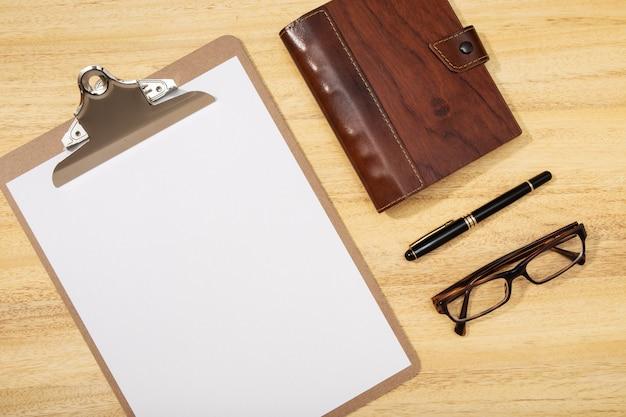 Biurko z płaskim stołem, widok z góry. obszar roboczy z pustym klipsem, długopisem, okularami i pamiętnikiem na drewnianym stole
